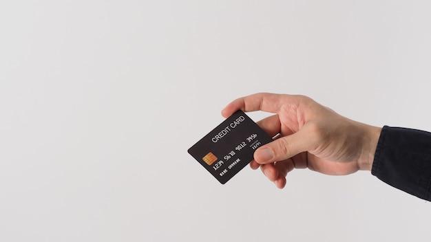 손은 흰색 배경에 고립 된 검은 신용 카드를 들고 있습니다. 아시아 남자 손입니다.