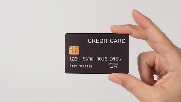 手は白い背景で隔離の黒いクレジットカードを保持しています。