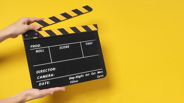 Рука держит доску с хлопушкой или доску с хлопушкой или сланец фильма. он используется в производстве фильмов и кино, киноиндустрии на желтом фоне.