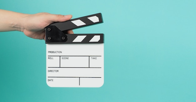 손은 클래퍼 보드, 클래퍼보드 또는 영화 슬레이트를 들고 있습니다. 영화 제작 및 영화 산업에서 그린 민트 또는 tiffany blue 배경에 사용됩니다.