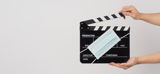 手は白い背景にカチンコまたは映画のスレートとフェイスマスクを保持しています。