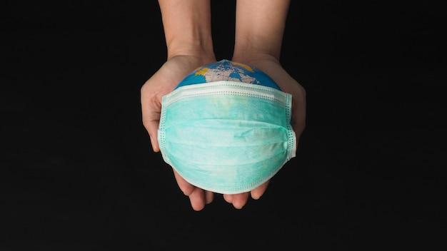 Рука держит земной шар и маску для лица на черном фоне. концепция covid-19.