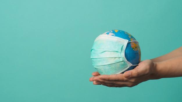Рука держит земной шар и маску для лица на зеленом или синем фоне тиффани концепция covid-19.