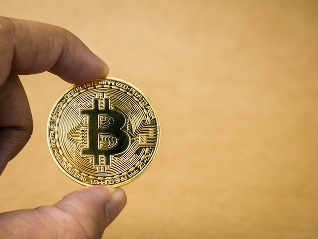 Hand is holding gold bitcoin.