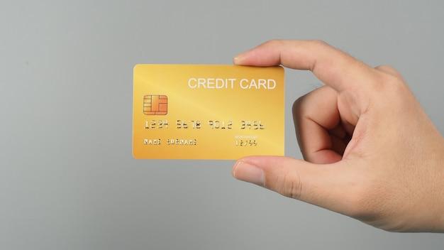 손은 회색 배경에 격리된 금색 신용 카드를 들고 있습니다.