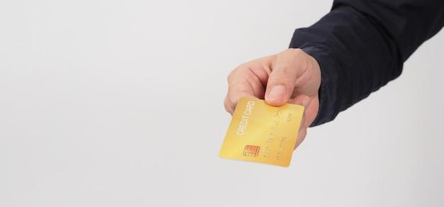 Рука держит золотую кредитную карту, изолированную на белом фоне. азиатская рука человека.