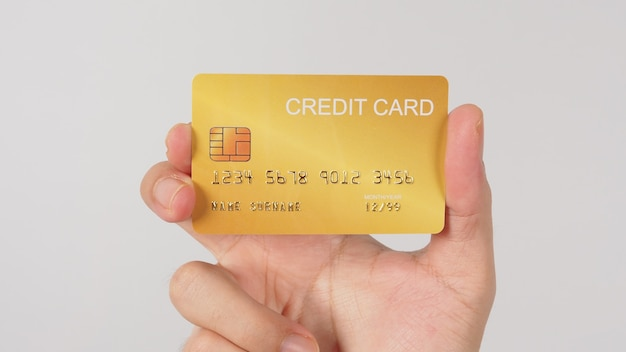 Hand is holding gold credit card isolated on white background.