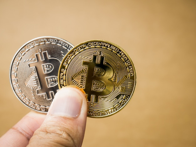 Hand is holding gold and silver bitcoin.