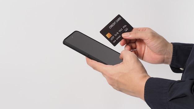 Рука держит мобильный телефон и черную кредитную карту на белом фоне.