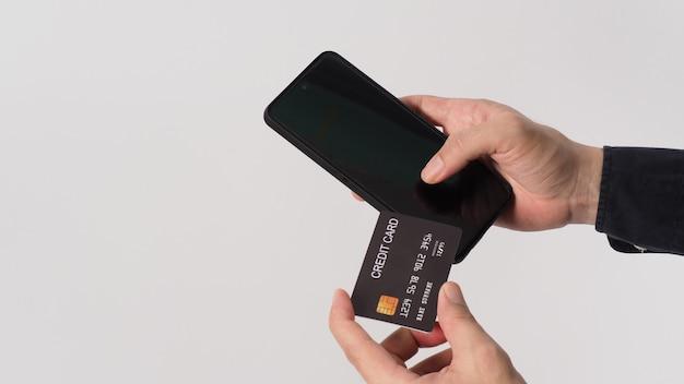 손은 흰색 바탕에 휴대폰과 검은색 신용 카드를 들고 있습니다.