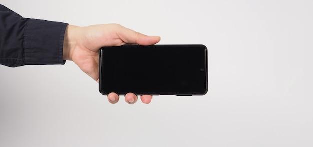 손은 흰색 배경에 고립 된 휴대 전화를 들고 있다.