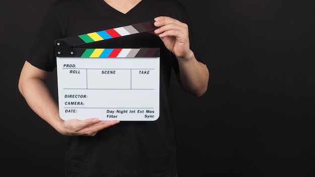 手は映画のスレートを持っています。それは黒い背景でビデオ制作や映画産業で使用されます。