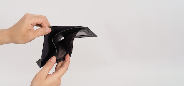 Hand is holding and open black empty wallet isolated on white background.