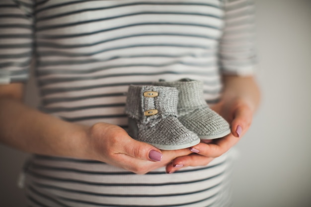 A hand is holding a pair of little shoes. it's a shoes for infant. mother and baby theme. pregnant woman. happiness