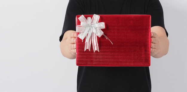 Hand is holding present or gift box wrap with red color paper on white background.