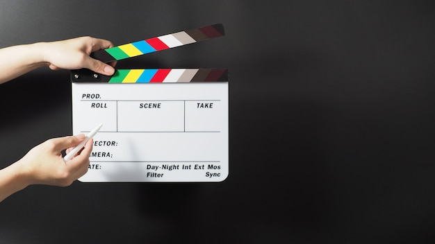 Рука держит доску с хлопушкой радуги или шифер фильма и маркер на черном фоне.