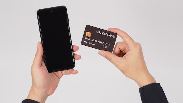 Рука держит смартфон и черную кредитную карту на белом фоне.