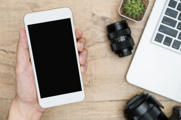 Hand is holding a smartphone with blank mockup screen above the photographer table.