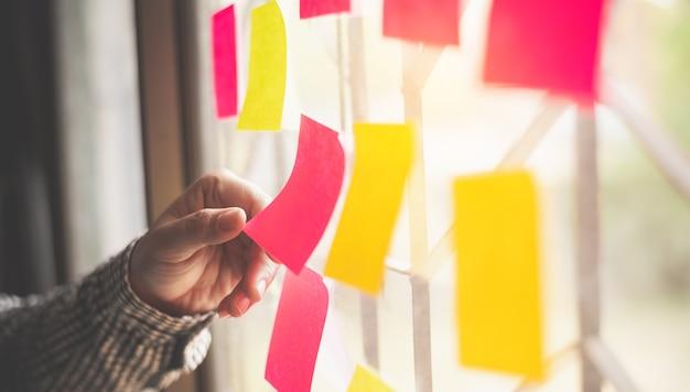 손은 글래스 벽에 붙은 노트를 잡고 있습니다. 개념 브레인 스토밍, 아이디어 공유.