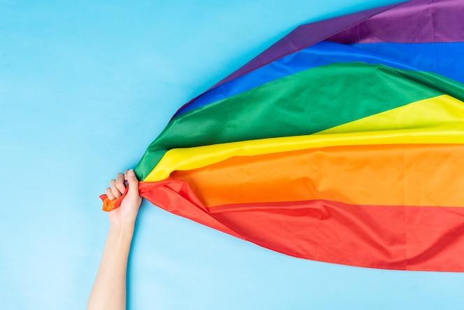 手は虹色の旗を持っています