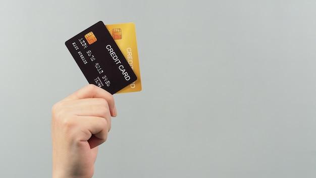 손은 회색 배경에 격리된 검은색과 금색으로 된 두 개의 신용 카드를 들고 있습니다.