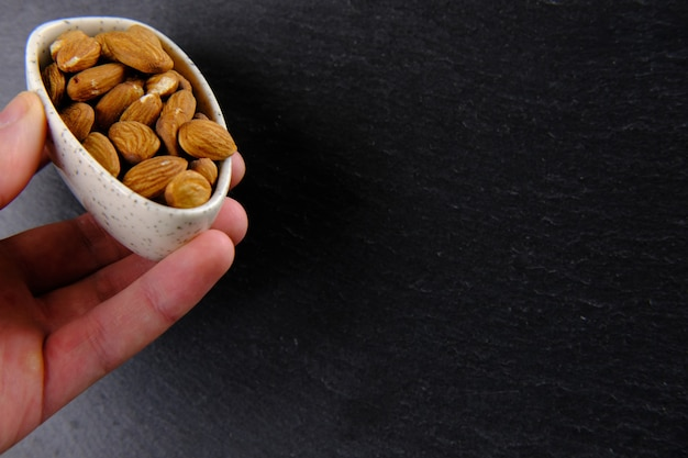 Hand is holding a white plate full of brown almonds on black
