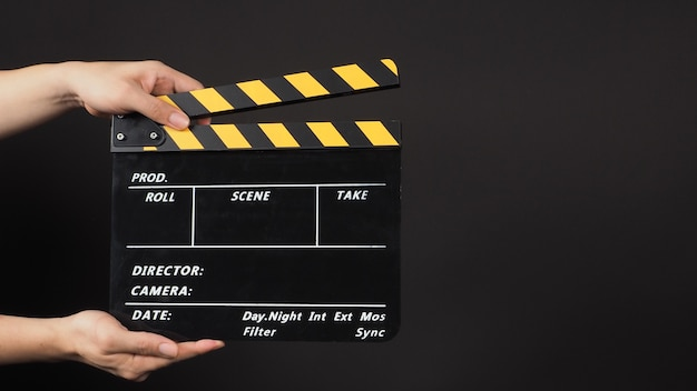 手は黄色と黒のカラー映画スレートを保持しています。それは黒の背景でビデオ制作や映画産業で使用されます。
