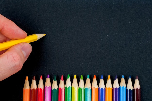 A hand is holding a yellow pencil on a black background next to the colored pencils. copy space.