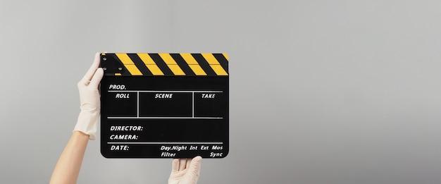 Рука держит желтый с черным цветом доски с хлопушкой и носит белую медицинскую перчатку. он используется в производстве видео и кино на сером фоне.