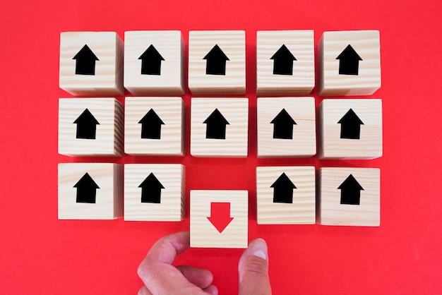 手は、赤い矢印が黒い矢印の反対方向を向いている木製のブロックを置いています。ユニークで、違った考えで、個性的で、群衆から際立っています