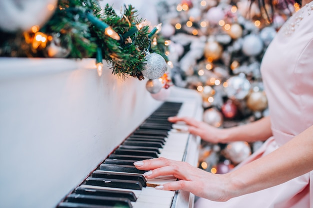 The hand is moving and playing the piano with lights and christmas trees decorated
