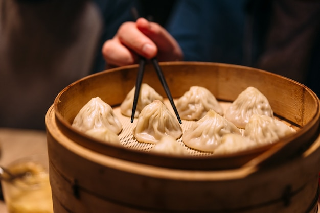 A hand is pinching xiao long bao (soup dumpling) with chopsticks from bamboo streamer.