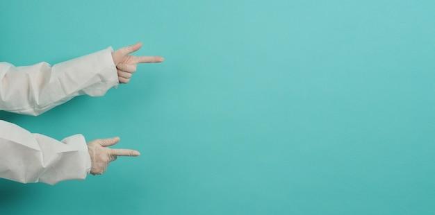 손이 손가락을 가리키고 파란색과 녹색 또는 tiffany blue 배경에 의료용 장갑과 ppe 슈트를 착용합니다.