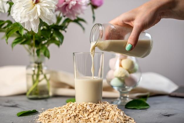 손은 천연 식물성 오트밀 우유 한 잔에 붓고 있습니다.
