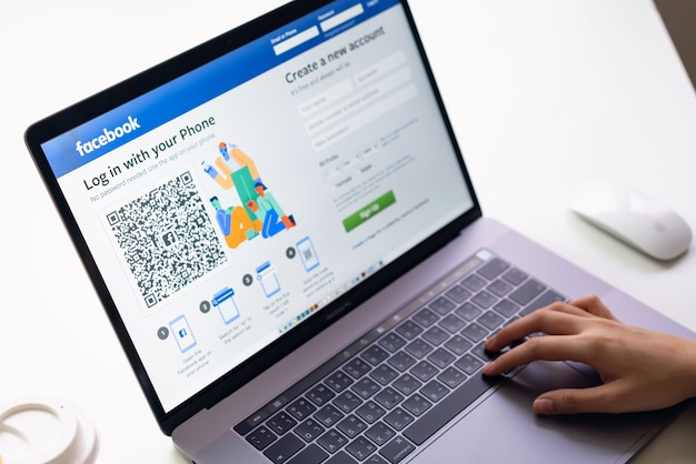 Hand is pressing the facebook screen on laptop