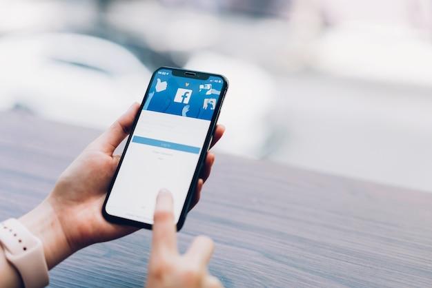 Рука нажимает на экран facebook на apple iphone x, социальные медиа.