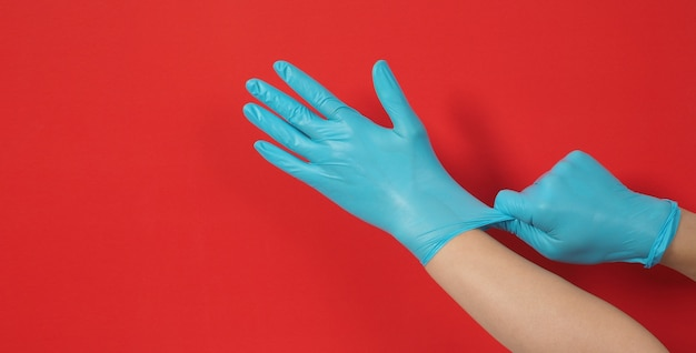 手は赤い背景に青いラテックス手袋または手術用手袋を引っ張っています。