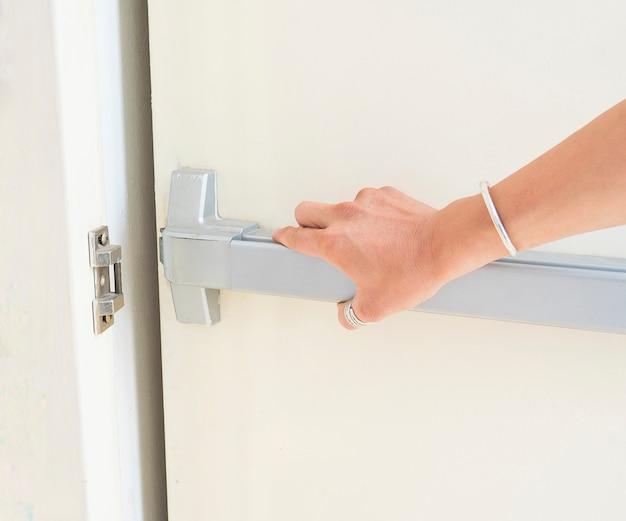 手が非常口のドアを押して開いている
