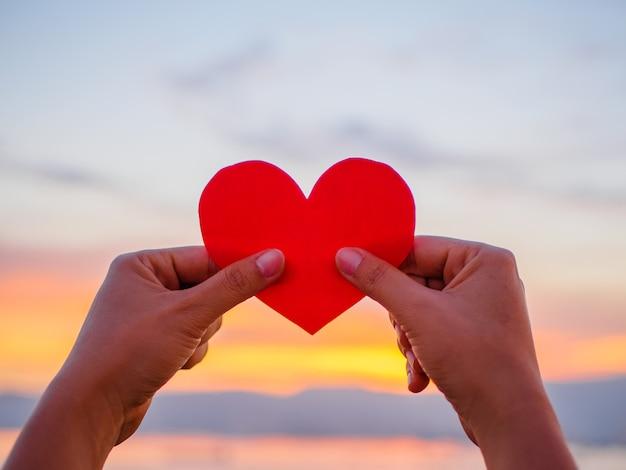 Рука поднимает красное сердце бумаги во время заката, день святого валентина