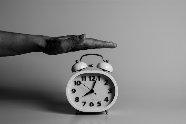 手が目覚まし時計を破壊し、停止するために叩いています。
