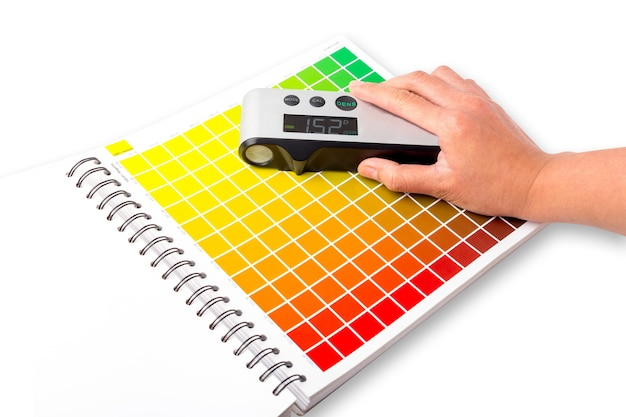 The hand is using a densitometer. a densitometer is an instrument used to measure the density of colors. it is commonly used in the printing industry and graphic design.