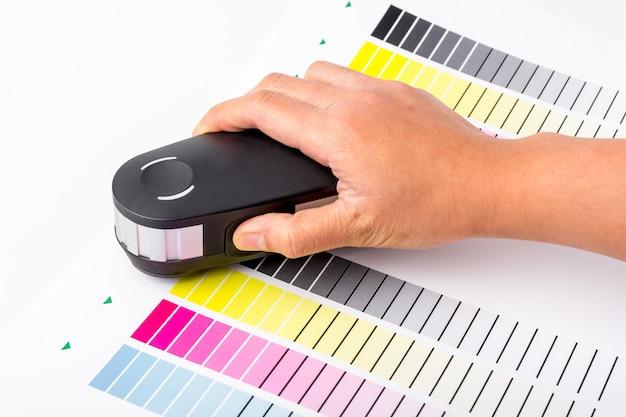 손은 테스트 색상에 대한 색상 차트 cmyk에 인쇄된 용지에 보정 기계를 사용하고 있습니다. 교정 기계는 인쇄 산업에 필수적인 장비입니다.
