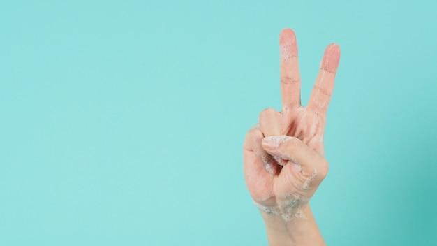 손은 승리 또는 v 손 기호이며 녹색 민트 또는 tiffany blue background.isolated에 거품 비누 거품이 있습니다.