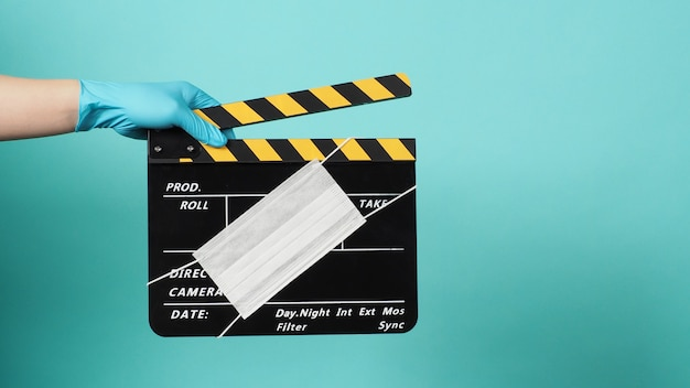 손은 파란색 의료용 장갑을 끼고 검은색 클래퍼 보드나 안면 마스크가 있는 슬레이트를 들고 있습니다. 녹색 또는 티파니 파란색 배경의 영화 제작 및 영화 산업에서 사용합니다.