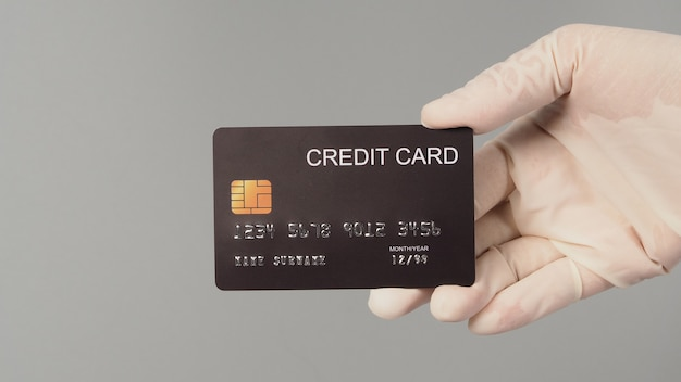 손은 흰색 의료용 장갑을 끼고 회색 배경에 격리된 검은색 신용 카드를 들고 있습니다.