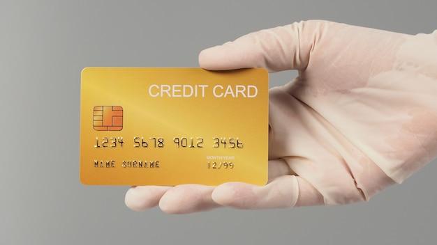 손은 흰색 의료용 장갑을 끼고 회색 배경에 격리된 금 신용 카드를 들고 있습니다.