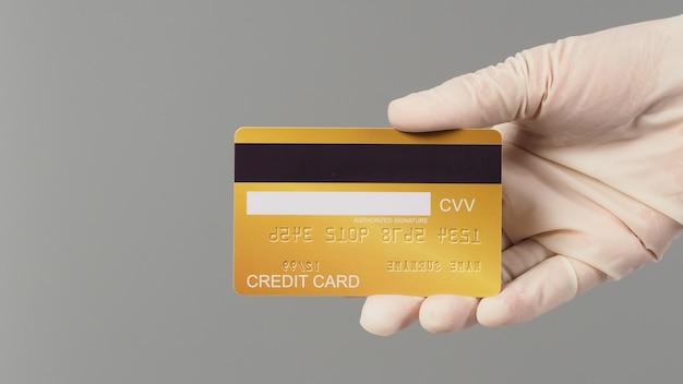 손은 흰색 의료용 장갑을 끼고 회색 배경에 격리된 금색 신용 카드 뒷면을 보여줍니다.