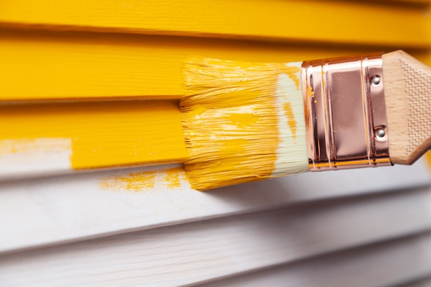 Hand iwith paintbrush painting natural wooden door with yellow paint