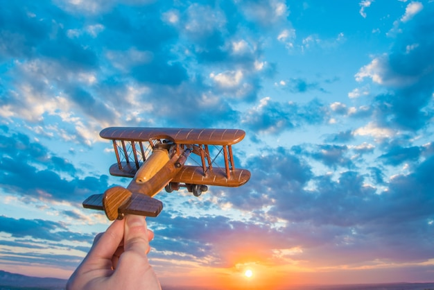 The hand launch toy plane on the background of a sunrise