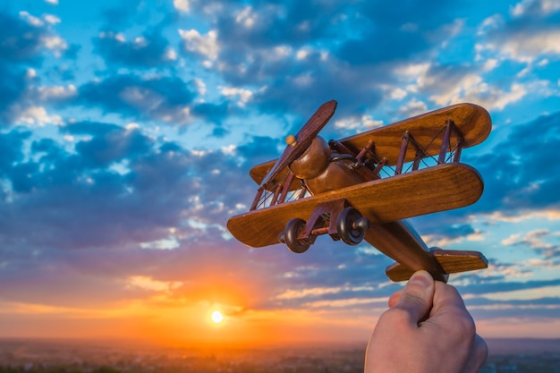 The hand launch toy plane on the background of a sunset